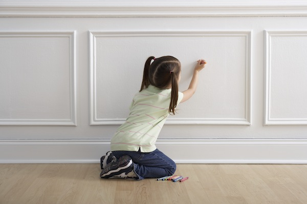 Girl coloring on wall